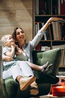 自宅のソファーに座っている小さな娘を持つ母