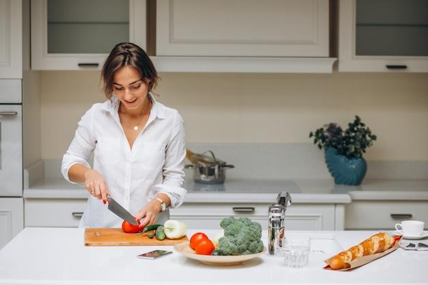 朝食を調理するキッチンで若い女性