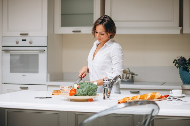 Молодая женщина на кухне приготовления завтрака