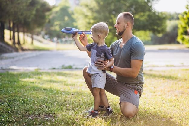 公園でおもちゃの飛行機で遊ぶ息子を持つ父