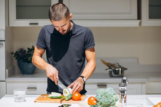 ハンサムな男が台所で朝食を調理