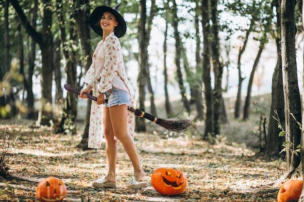 Молодая женщина, одетая в шляпу с метлой на хэллоуин в лесу