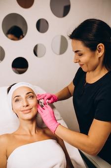 Косметолог делает уколы на лице женщины в салоне красоты