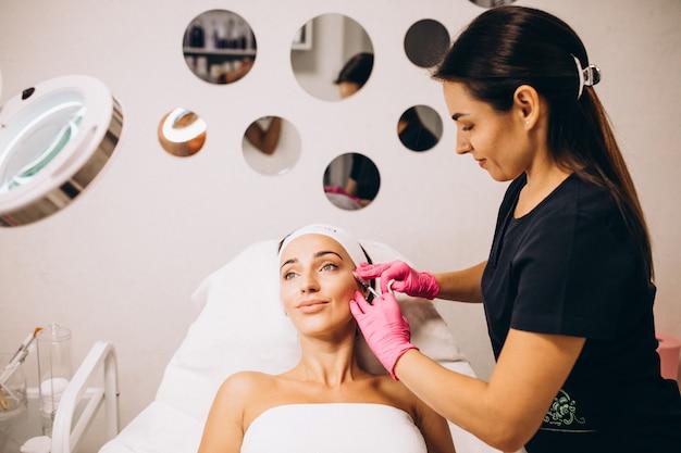 ビューティーサロンで女性の顔に注射を行う美容師