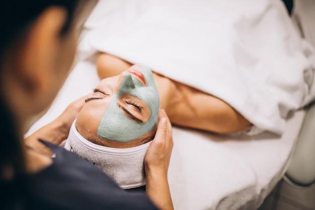 ビューティーサロンでクライアントの顔にマスクを適用する美容師
