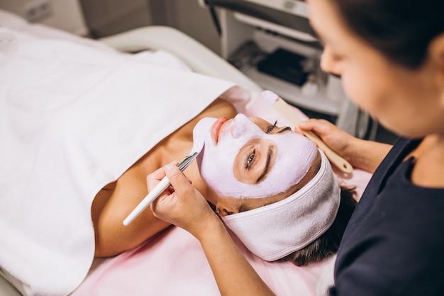 Косметолог наносит маску на лицо клиента в салоне красоты