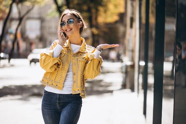 通りで外の電話を使用して黄色のジャケットの若い女性