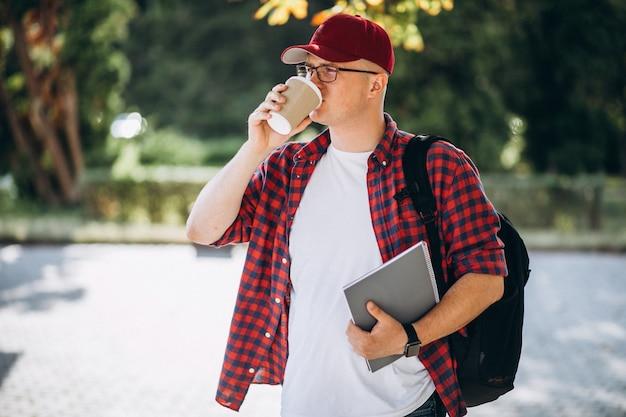 Молодой студент пьет кофе с ноутбуком в парке