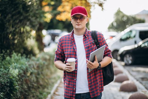 公園のラップトップでコーヒーを飲む若い男性学生