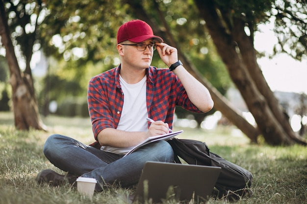 Молодой студент работает на компьютере в парке