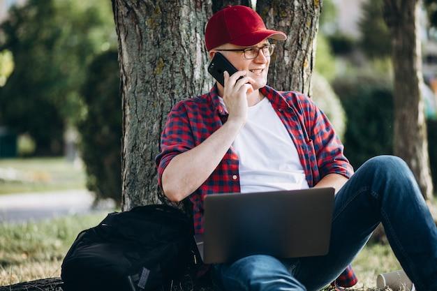公園内のコンピューターに取り組んでいる若い男性学生
