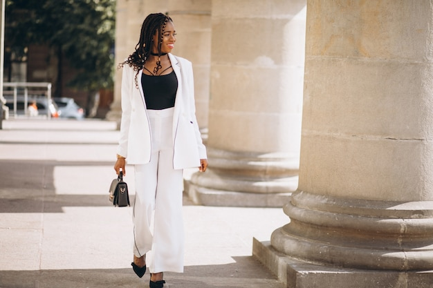 通りの外の白いスーツに身を包んだ若いアフリカ人女性