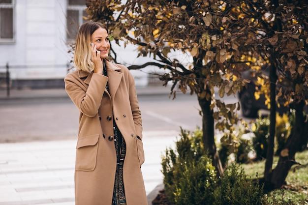 通りの外の電話を使用してベージュのコートの若い女性
