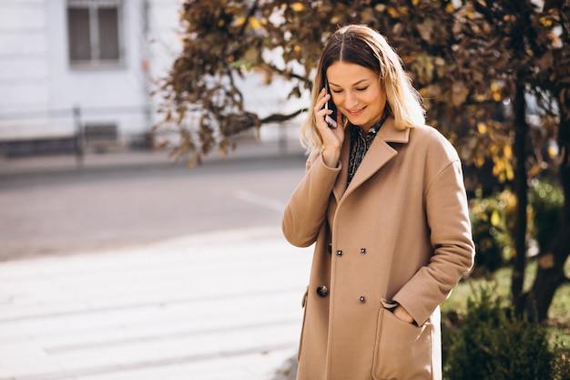 Молодая женщина в бежевом пальто с помощью телефона на улице