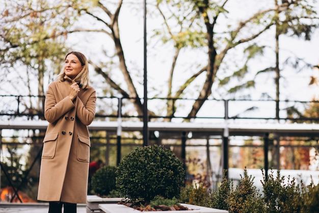 Красивая женщина в бежевом пальто снаружи в парке