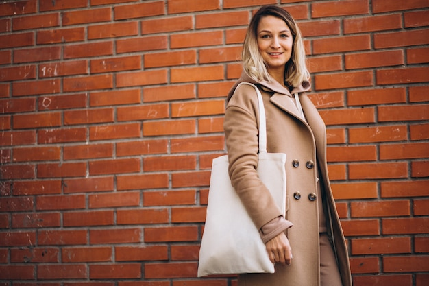 レンガの壁でバッグを持つ若い女性