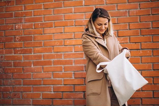 Молодая женщина с сумкой у кирпичной стены