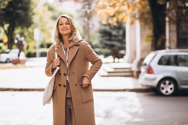 通りで買い物袋とベージュのコートの女性