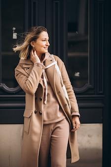 Женщина в бежевом пальто с хозяйственной сумкой на улице