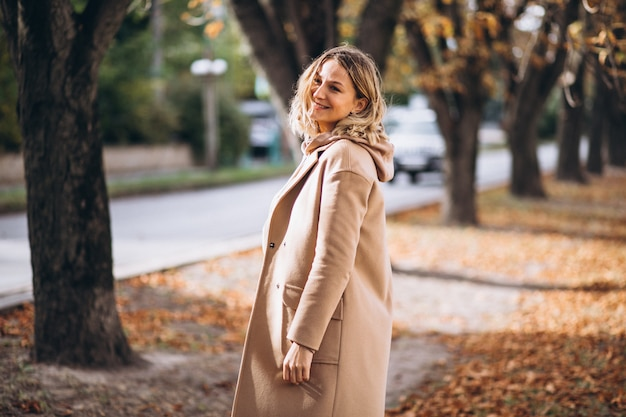 秋の公園で外にベージュのスーツの若い女性