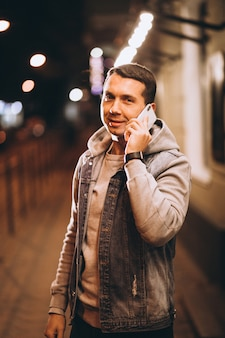 Молодой красавец с помощью телефона ночью на улице