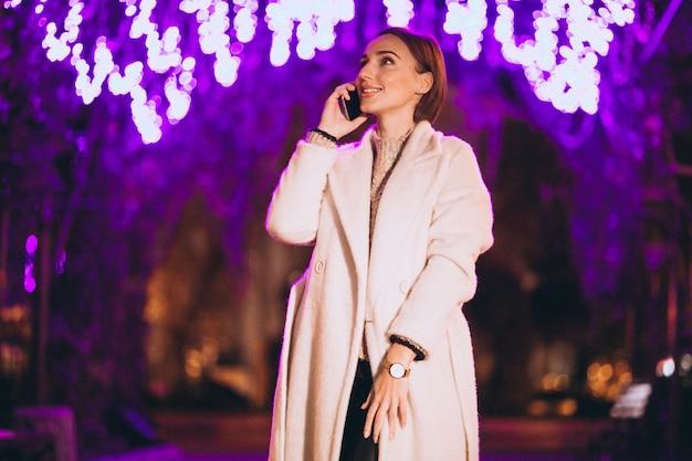 夜の街の外の電話を使用して若い女性