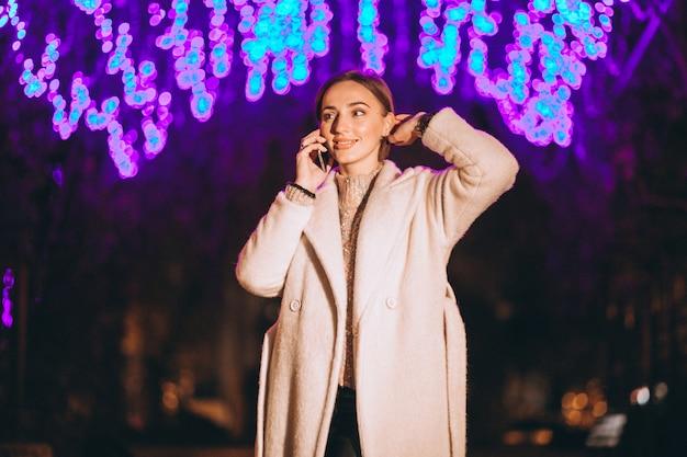 Молодая женщина с помощью телефона на улице ночью