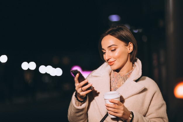 夜の街でコーヒーを飲む若い女性