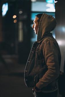 夜通りを歩いて若いハンサムな男