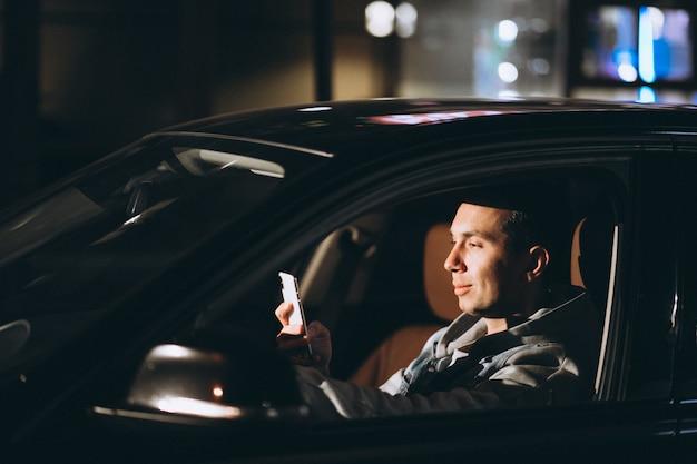 Молодой человек за рулем своего автомобиля в ночное время и разговаривает по телефону