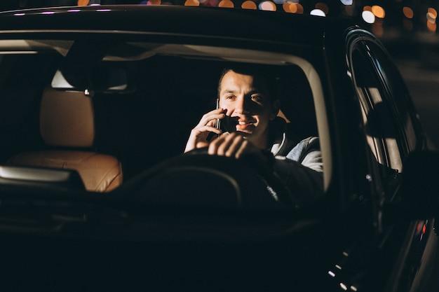 道路で車を運転し、電話で話している男性