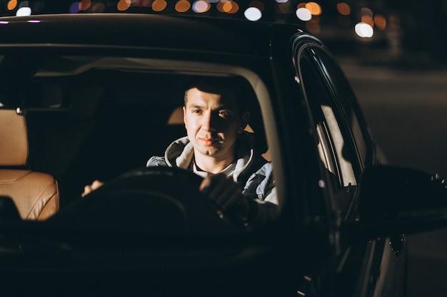道路で車を運転する男