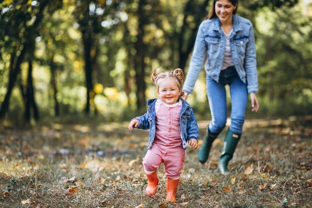 Молодая мать с маленькой дочерью в осеннем парке