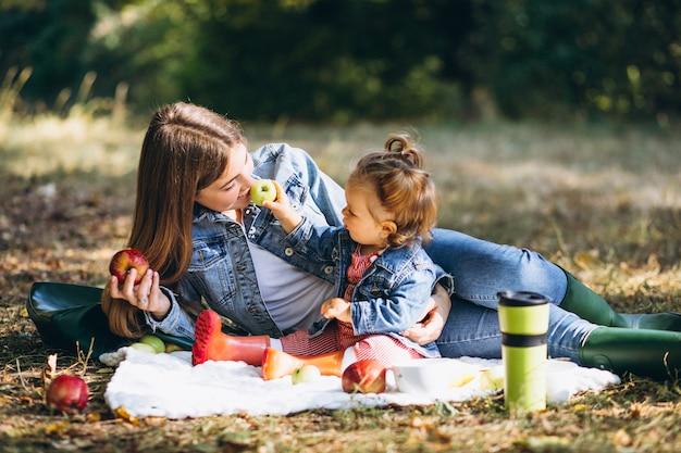 ピクニックを持つ秋の公園で彼女の小さな娘を持つ若い母親