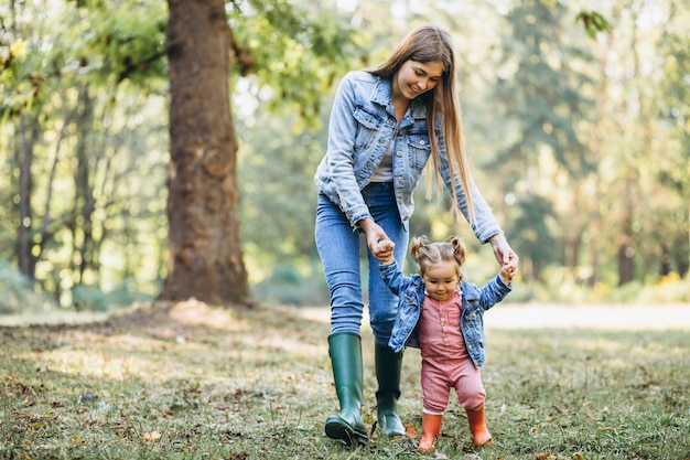 秋の公園で彼女の小さな娘を持つ若い母親