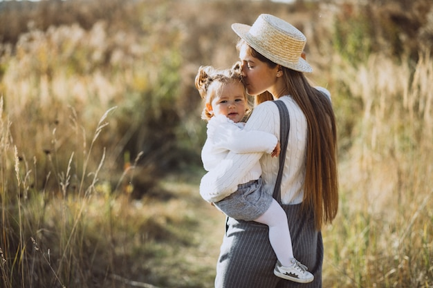 秋のフィールドで彼女の小さな娘を持つ若い母親