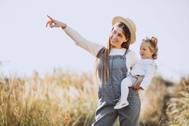 Молодая мать с маленькой дочерью в осеннем поле