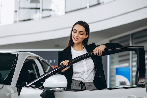 車のショールームで車を選ぶ女性