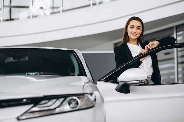 Женщина выбирая автомобиль в автосалоне