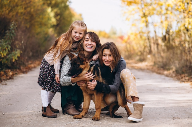 秋の公園で犬と子供を持つ母
