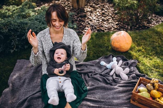 裏庭でピクニックを持つ彼女の幼い息子を持つ母