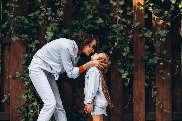 裏庭で彼女の小さな娘を持つ女性