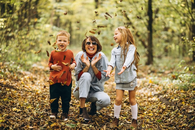 秋の公園で彼女の幼い息子と娘を持つ母