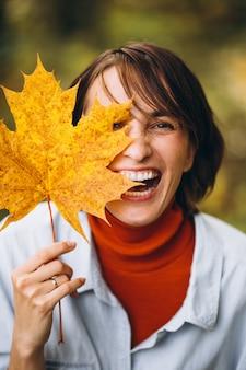 葉だらけの秋の公園で若い美しい女性