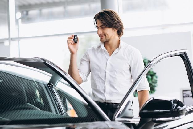 車のショールームでキーを保持している若いハンサムな男
