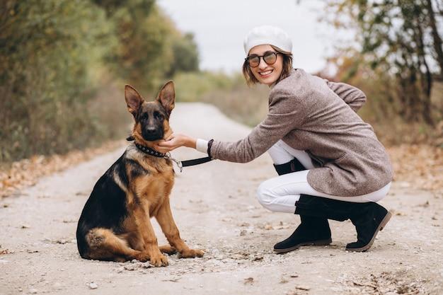 秋の公園で彼女の犬を歩いて美しい女性