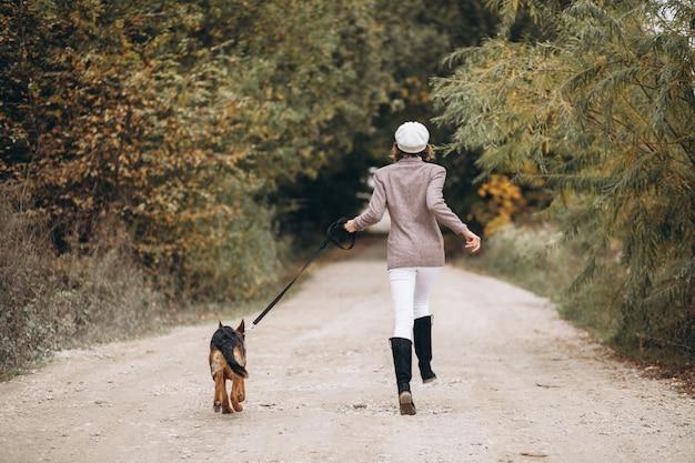 Красивая женщина выходя ее собака в парке осени