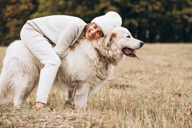 Красивая женщина выходя ее собака в поле