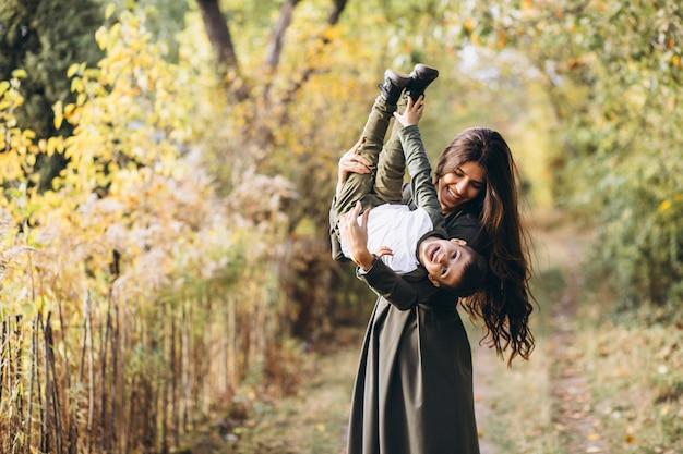 秋の公園で幼い息子を持つ母