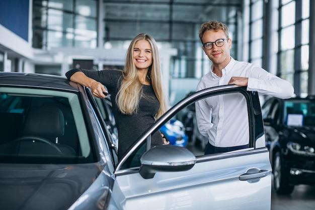 たくさんのことをしている自動車ショールームで幸せな顧客